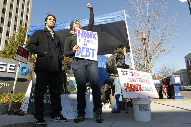 University of Kentucky students Alexander Southard, left, and Cheyenne Hohman, who regularly demonstrate with the Occupy Lexington group at Main Street and Esplanade, were there on Friday.