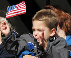 Vine Grove resident Wesley Betson, 4, waves American flags during the Hardin County Veterans Day celebration Satuday at Optimist Park in Vine Grove.