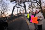 Ruby Layson, right, and Dawn Hale stand by the road and hold up signs on the Singing Bridge.