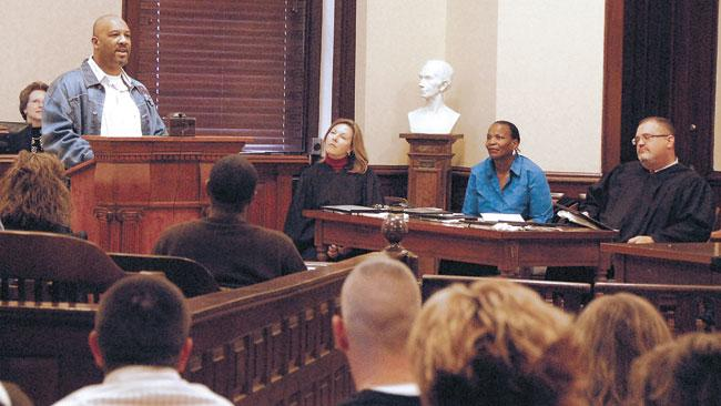 Circuit Clerk Paula Joslin, left, Clark Circuit Judge Jean Chenault Logue, guest speaker Tayna Fogle and District Judge Earl-Ray Neal look on as drug court graduate Herbert Beasley talks to fellow graduates