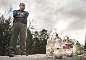 Detective Tim Robinson of the Warren County Sheriff's Office stands Monday beside HCL generators on Garrett Hollow Road after they were found in the woods at a meth dumpsite. Bowling Green-Warren County D