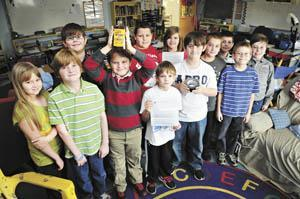 Some of Deedy Whittamore's fourth and fifth-grade class members at Holy Trinity Lutheran School hold up some Made in America items Friday that they found as part of their recent discussions about the farming out of manufacturing and packaging jobs.
