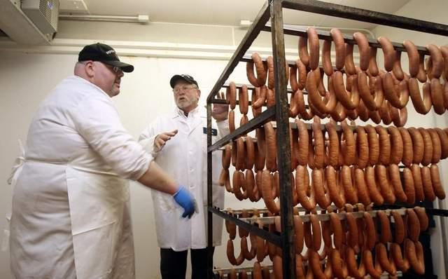 Steve Brooks (right), owner of Brooks Meats, and Stefan Neumann, a German master sausage maker who works for Brooks, talk in the cool down room of Brooks' processing facility where fresh cheese and regular metts are cooling down.
