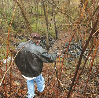 Bishop Street resident Dennie Comer, above, said he was surprised to find a large illegal dump site in a well-hidden gully only about 20 yards from his home last week. He's lived at the residence over two years and said he did not realize it was there.
