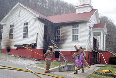 Firefighters were busy Friday afternoon carrying items from inside the Black Mountain Missionary Baptist Church. One firefighter carried a cross from the church to put in a safe place outside.