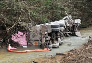 A Kentucky Powder Company tanker truck rests on its side in a creek at Little Robinson Creek following a crash Monday. The truck spilled about 15,000 pounds of a pink, powdery blasting agent, prompting officials to evacuate nearby residents.