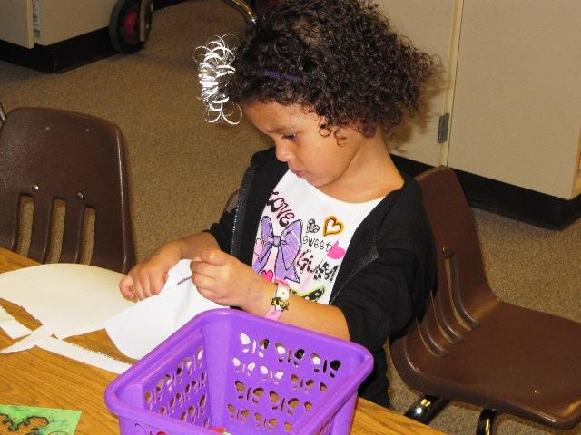 A preschooler works with scissors and paper at Dixie Elementary School in Lexington.