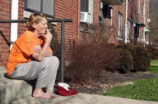 "Judy Jackson smokes a cigarette as she sits on the porch of her home in Latonia Terrace. Jackson called a proposal to ban smoking in public housing ""outrageous."""