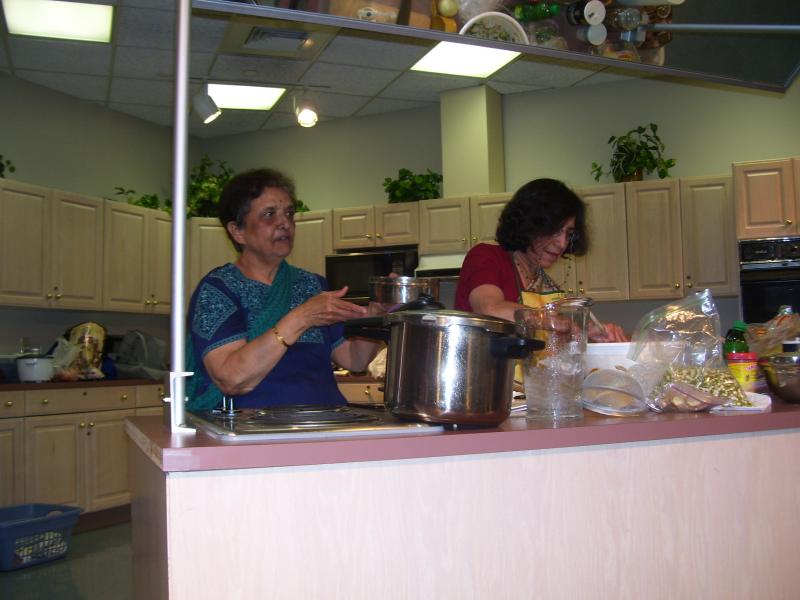 Suhasini Bhapkar and her assistant busy at the teaching cooking station