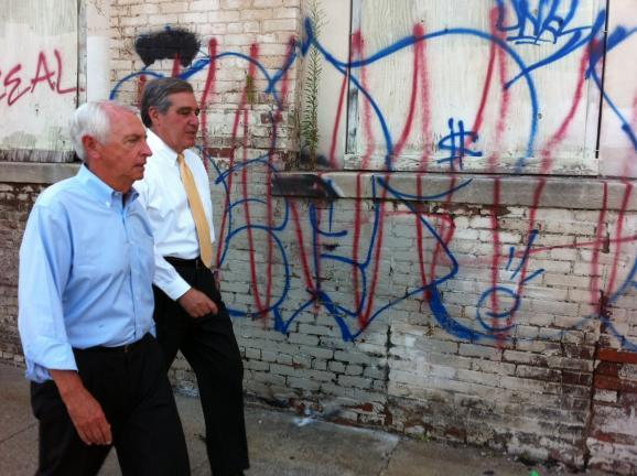 Gov. Beshear and Lt Gov. Jerry Abramson walk past one of the two buildings that will be preserved.