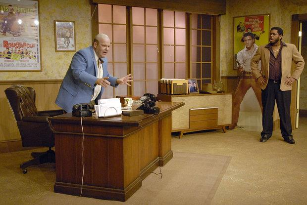 """The Colonel (left, played by Tim """"X"""" Davis) explained to Candy (played by Spencer Maguire) how he needs to find Elvis to pay off a gambling debt."""