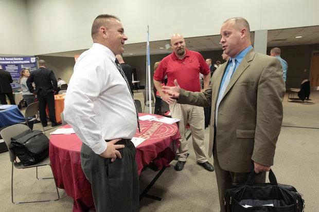 Robert Green, left and John Clark, center of Schwan's home delivery grocery store spoke with Charles Parsley during a job fair for veterans at Northeast Christian Church in Lexington on Oct. 17.