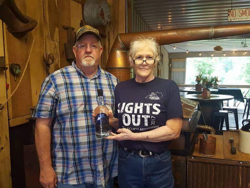 Distillery co-owners Arlon Jones and Peg Hays showcase a bottle of their limited edition eclipse moonshine.