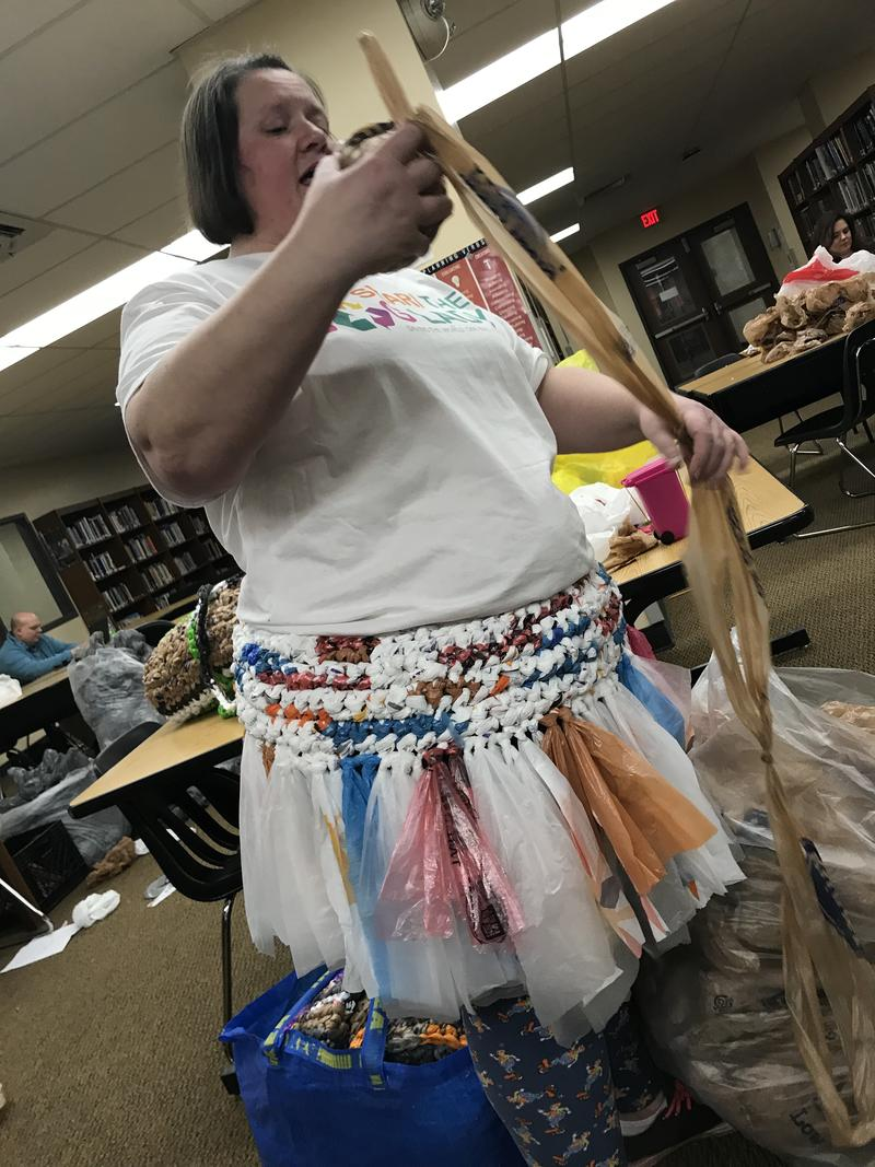 Shari demonstrates how to transform plastic bags into plarn at Holmes High School
