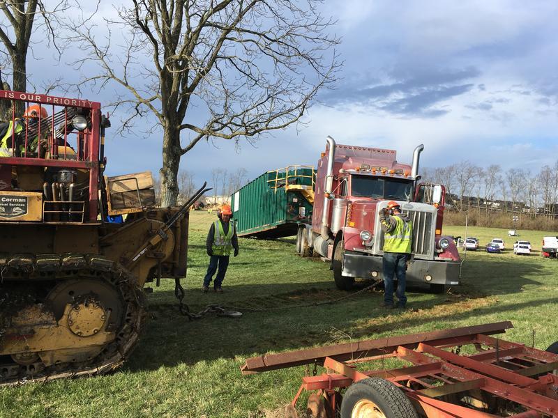 Trucks Pull Cargo Units Away from Scene