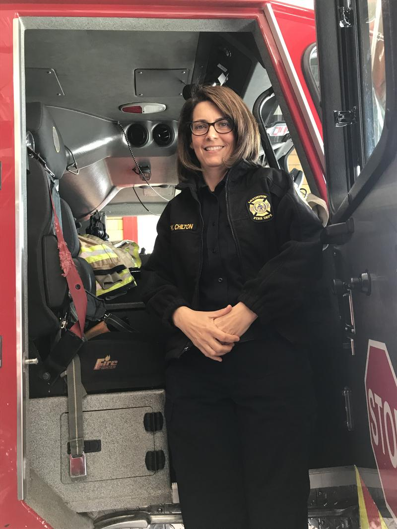 Lexington's first female fire chief poses on one of the fire engines