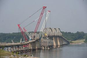Cranes lift a new span for the Eggners Ferry Bridge into place on Tuesday. State officials say the repairs are expected to be complete by Memorial Day.