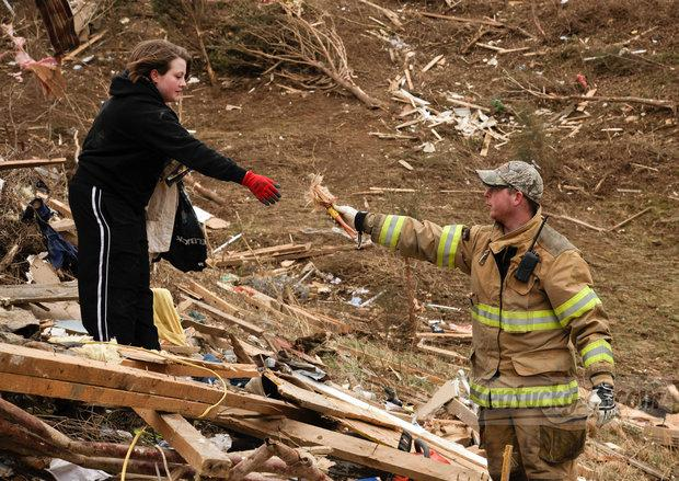 Volunteer firefighter Aaron Stamper and Olivia Gronlund pick through debris looking for personal belongings for their friends Beverly and Ronnie Bowman whose house was destroyed on Opossum Hollow Road.