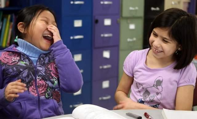 Trang Nguyen (left) and Juana Ortega, third-graders at River Ridge Elementary School, share a laugh during English Language Learners class. The class is for students who are not native speakers of English.