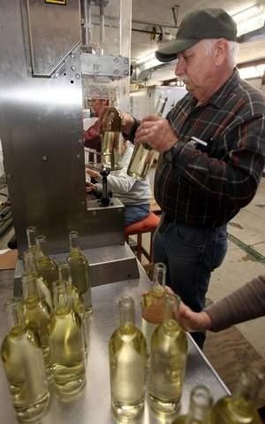 Dennis Walter, who owns StoneBrook Winery, Camp Springs, uses a pneumatic corking machine to set corks in bottles of pear wine. A bill filed by Rep. Dennis Keene would provide for separate liquor licenses.