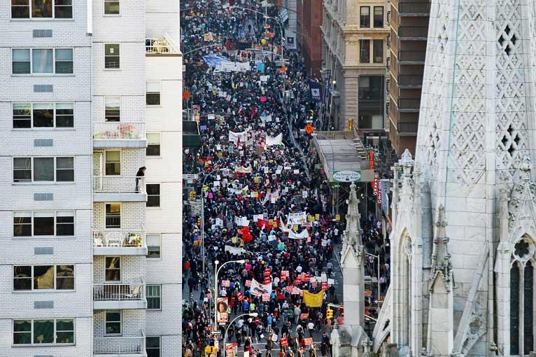 Protestors marching down a street in New York, as seen from above.