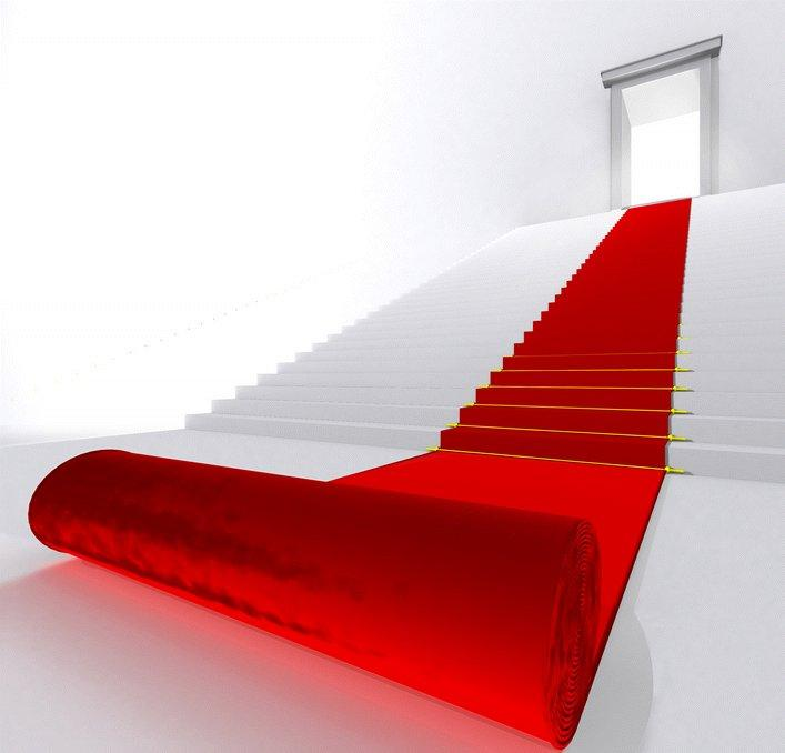 A red carpet rolling down white stairs.