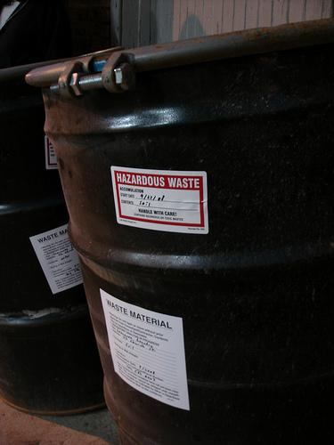 A hazardous waste barrel with a label.