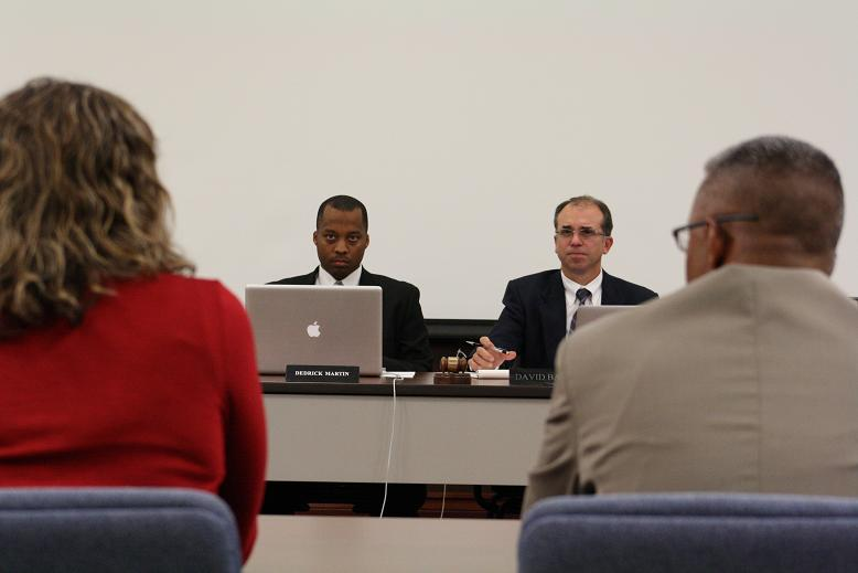 Ypsilanti Superintendent Dedrick Martin (left center) and school board President David Bates (right center) watch a presentation on the district's food service operation.