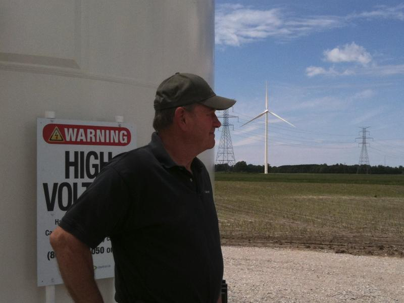 Ralph Lundgren in front of one of the five turbines on his land in Lake Winds Wind Park