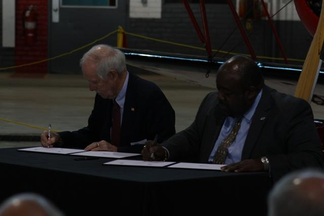 Yankee Air Museum Chair Ray Hunter (l) and RACER Trust Administrative Trustee Elliott P. Laws sign purchase agreement.