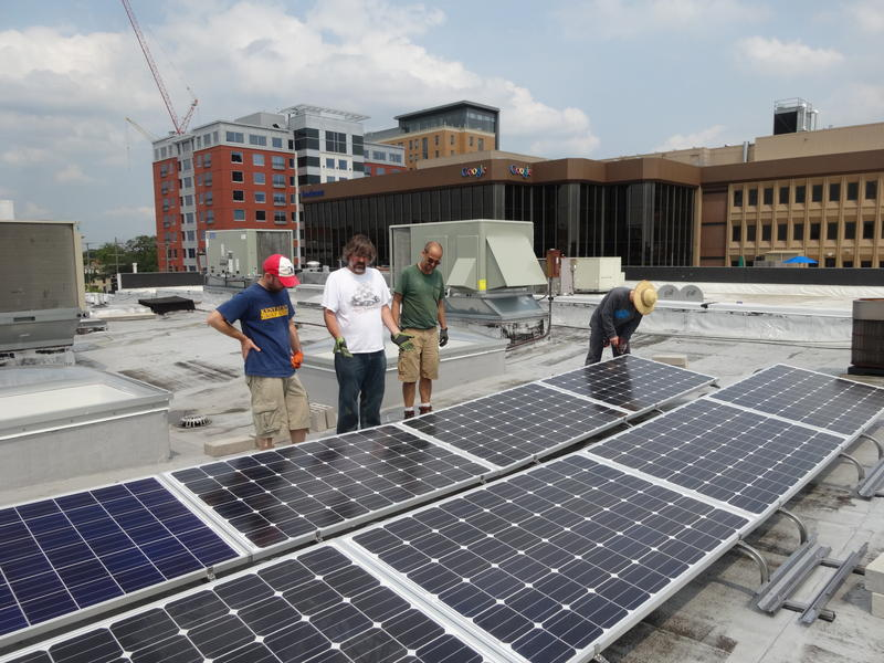 """Installing solar panels on the roof of the Ecology Center building in downtown Ann Arbor."""