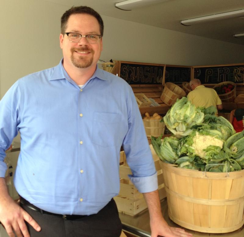 The clinic's executive director Matt Hudson inside their new free produce location as fresh vegetables are arriving for distribution.