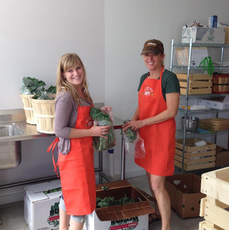 Eastern Michigan University student Tarah Hipple (left) who volunteers at the produce stand helps Hope Clinic board of directors president Greta Buck (right) arrange free produce for community pick up.