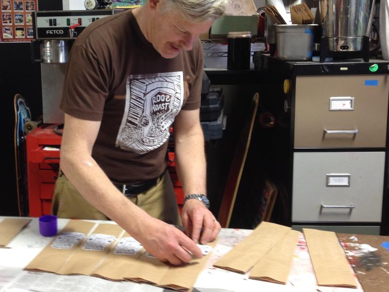 John Roos affixing his handmade labels to coffee packages