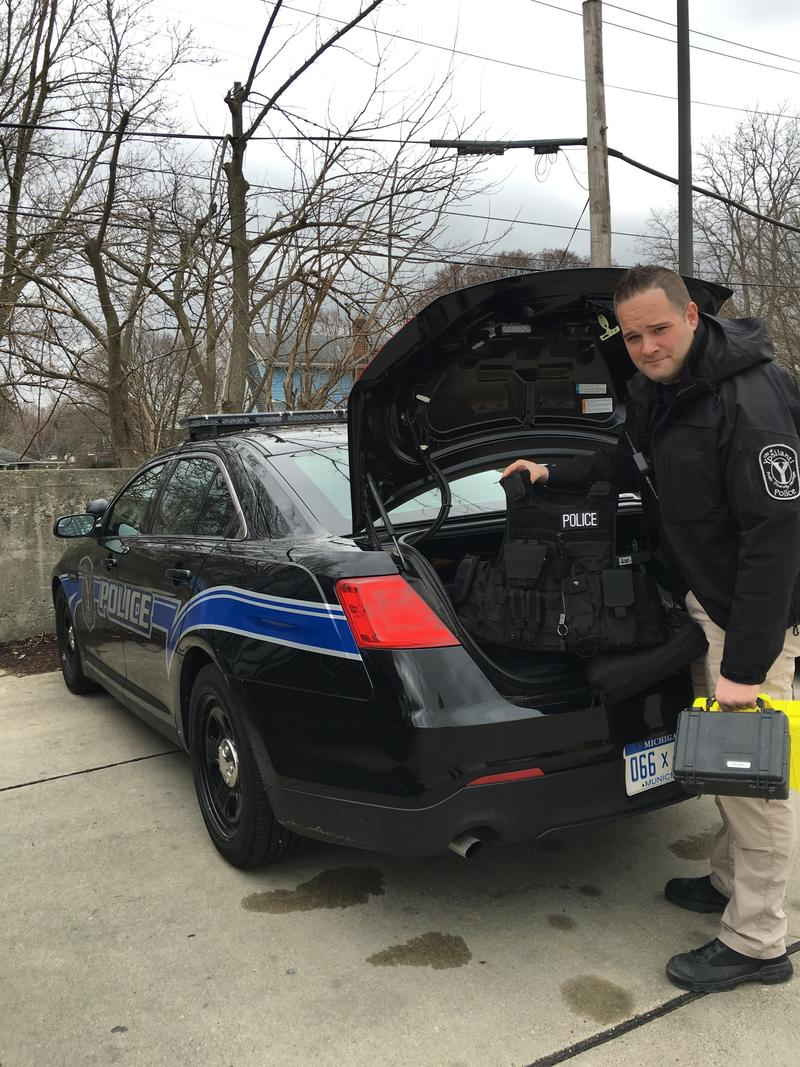 Officer Harrison loads police equipment into the cruiser before leaving to patrol the city.