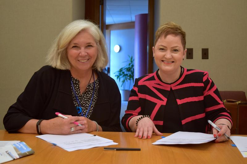 AADL Director Josie Parker and AAPS Superintendent Jeanice Swift sign the agreement on June 20, 2016