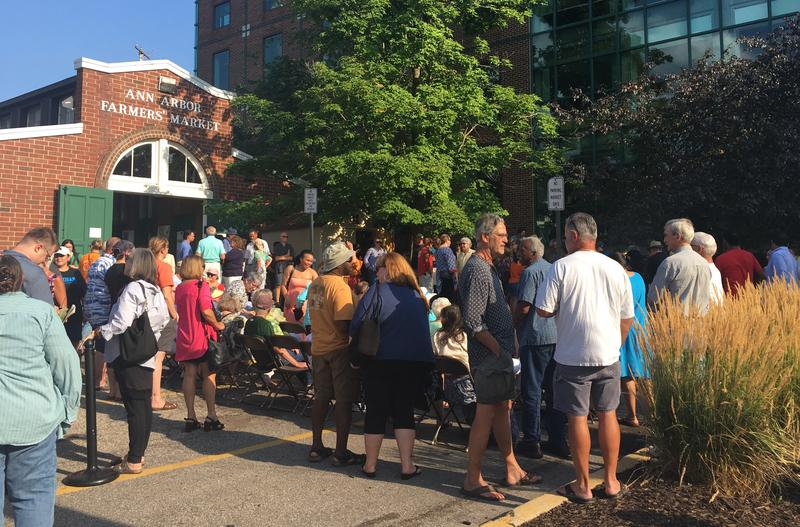 Crowd gathered Wed evening in Ann Arbor's Kerrytown market for unveiling of Adirondack chairs honoring Coleman Jewett