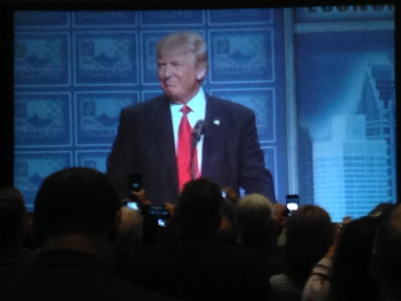 Crowd watches a large screen as Republican presidential candidate Donald Trump takes the stage before a crowd of 1,500 at a Detroit Economic Club lunch.