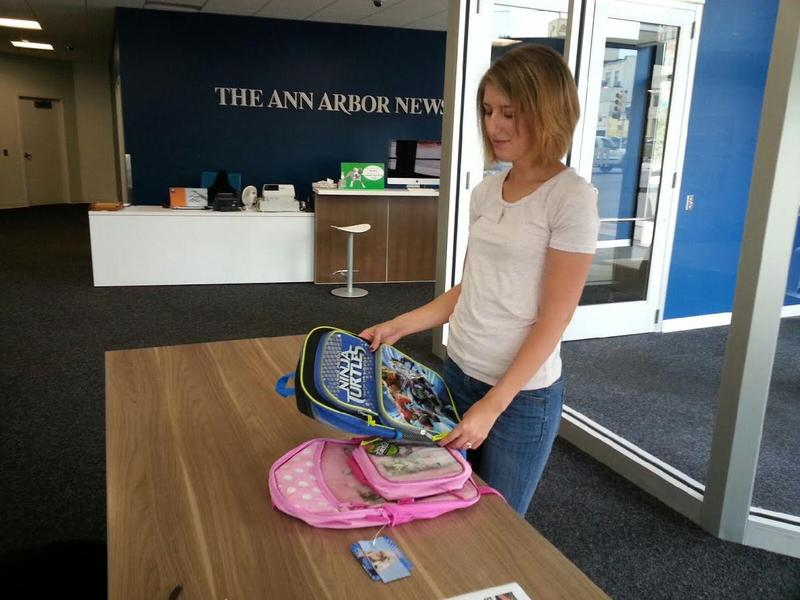 Lauren Slagter from The Ann Arbor News holds backpacks that were donated.