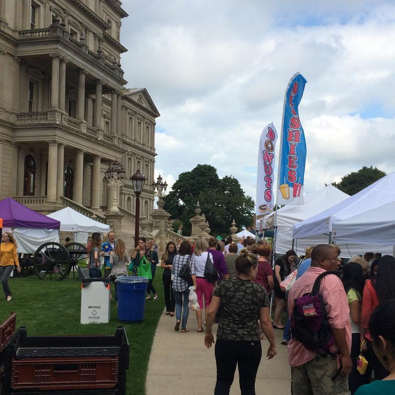 Lawmakers and regular folks stroll the farmers market at the state Capitol.