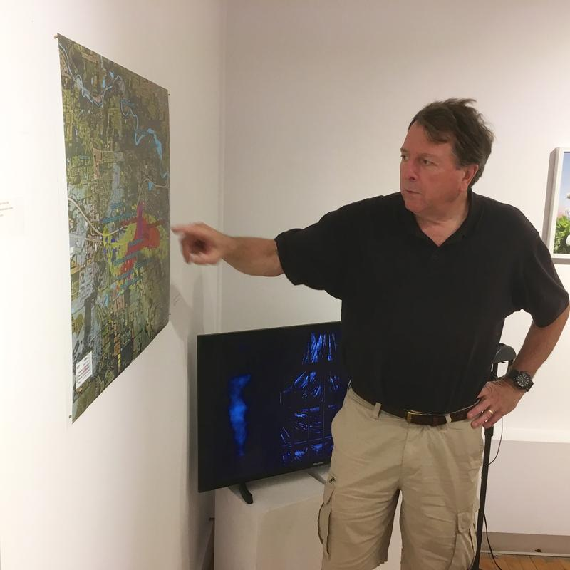 """Roger Rayle with his plume map at the Ann Arbor Art Center Re: Formation Exhibit,"