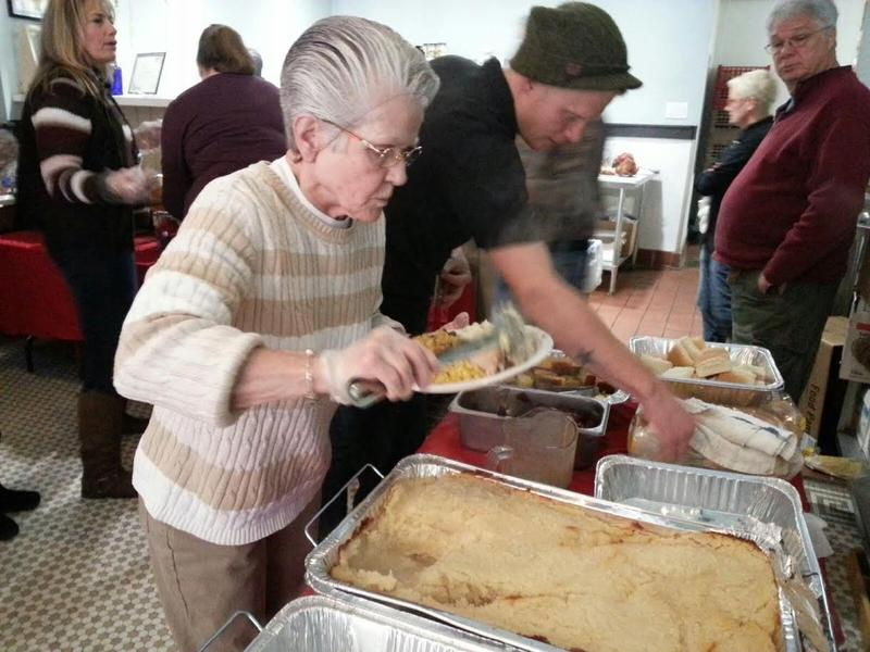 Volunteers serve food for the holiday dinner.