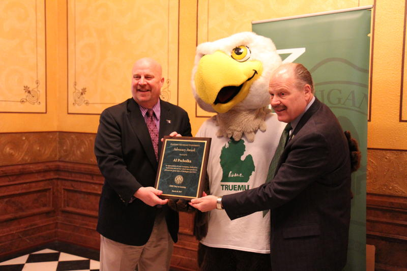 EMU President James Smith and Swoop present an award to state Representative Al Pscholka.