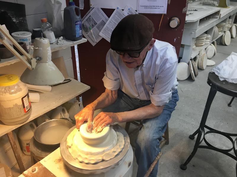 J.T. Abernathy molding a clay pot.