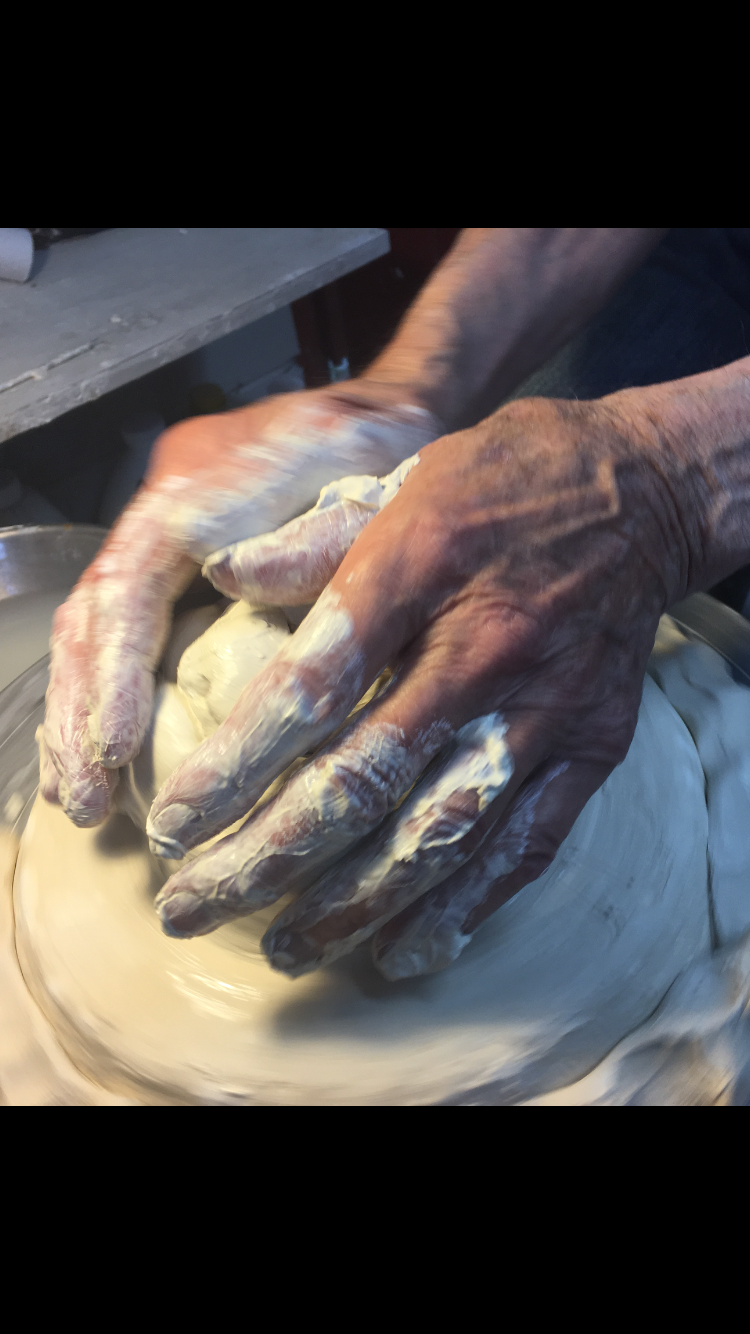 Abernathy's hands molding the pot.
