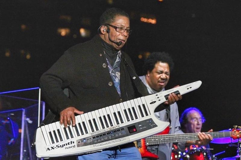Herbie Hancock plays the keytar - a hybrid portable keyboard/guitar - onstage at the 38th annual Detroit Jazz Festival on Friday, September 1. Behind Hancock is bassist James Genus and drummer Vinnie Colaiuta.