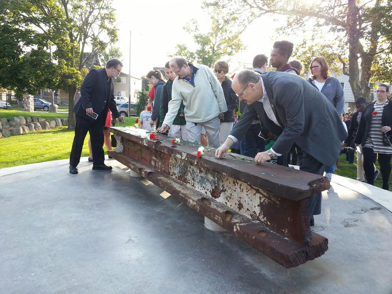 EMU president James Smith on the right places a carnation over a beam that came from the World Trade Center.