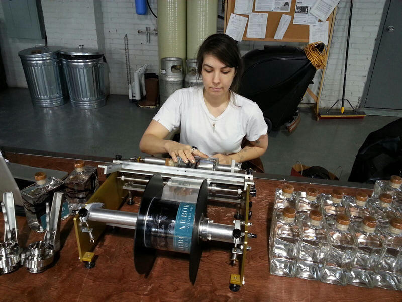 Employee Elissa Hughes labels bottles.  All bottles are labeled by hand.