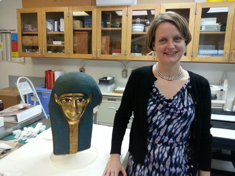Associate Curator of Conservation Suzanne Davis standing next to an Egyptian mask.
