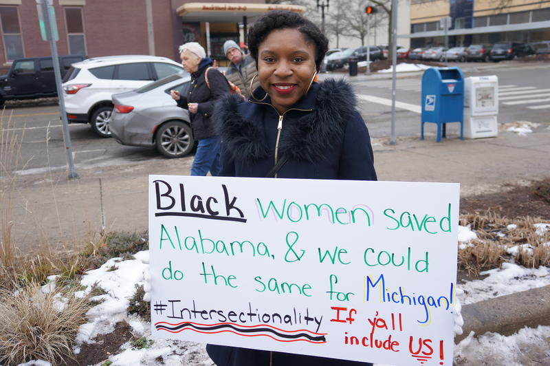 Myya Jones of Detroit holds her sign for the Women's March in Lansing.